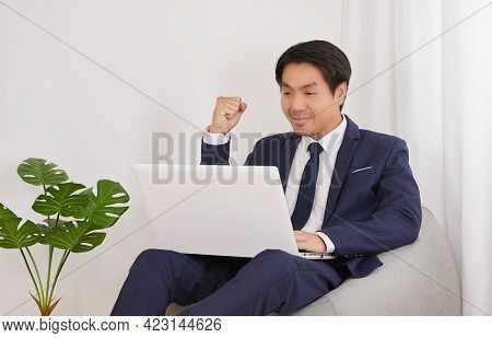 Asian Financial Advisor Success Smile Front Laptop In Home Office. Businessman Work At Home For Soci