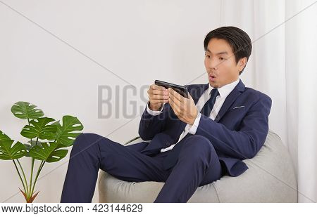 Asian Financial Advisor Shock With News And Sit On Bean Bag In Home Office. Businessman Work At Home
