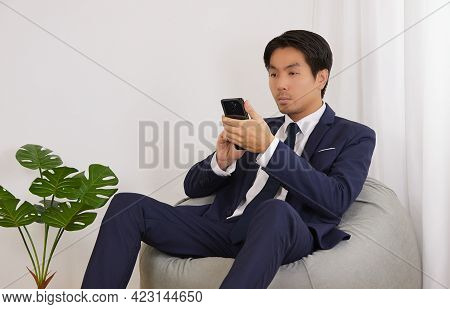 Asian Financial Advisor Touch Smartphone Or Mobile Phone On Bean Bag In Home Office. Businessman Wor