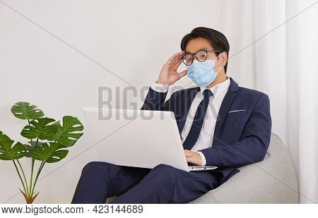 Asian Financial Advisor Wear Face Mask And Glasses Headache From Working In Home Cafe Office. Busine
