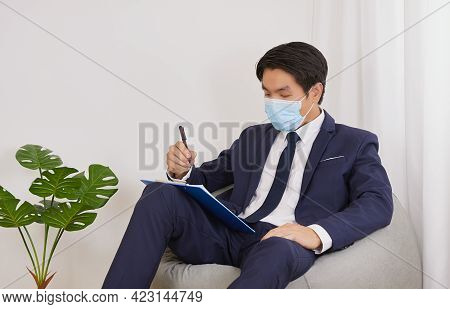 Asian Financial Advisor Wear Face Mask Checking Financial Statement On Clipboard In Home Cafe Office