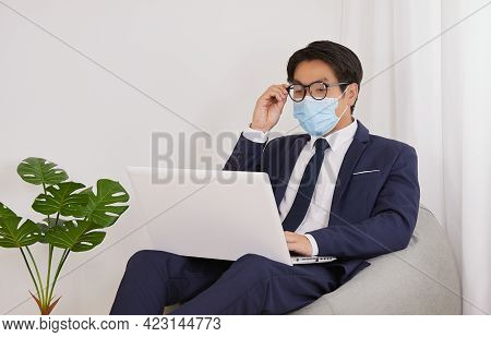 Asian Financial Advisor Wear Face Mask Hold Glasses Use Laptop In Home Cafe Office. Businessman Work