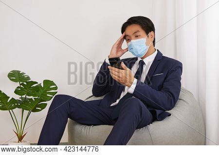 Asian Financial Advisor Wear Face Mask Serious Thinking On Bean Bag In Home Cafe Office. Businessman