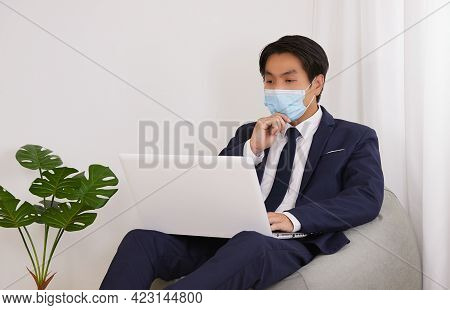 Asian Financial Advisor Wear Face Mask Use Laptop And Serious Thinking On Bean Bag In Home Cafe Offi
