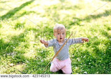 Small Child Is Kneeling On A Green Lawn And Holding A Twig In His Hands