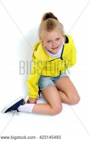 Happy Six Years Old Girl Sitting On Floor. Adorable Smiling Blonde Girl Posing Against White Backgro
