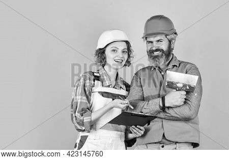 According To Plan. Discussing Renovation With Contractor. Plastering Works. Couple Look Documents. W