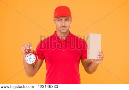 Take Your Shopping Time. Delivery Man Hold Clock And Box Yellow Background. Online Shopping. Cyber M