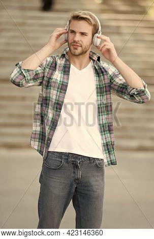 Stay Tuned. Handsome Man Wear Headphones Outdoors. Modern Music. Modern Day Device. Hi-fi Audio. New