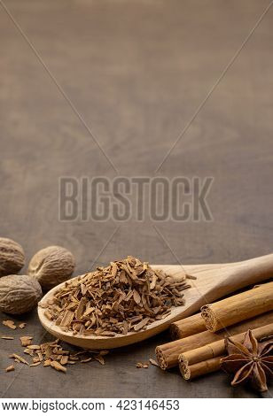 Wooden Spoon With Crushed Cinnamon, Cinnamon Rolls, Star Anise And Whole Nutmeg. Brown Background, C