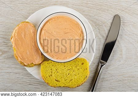 White Glass Bowl With Creamy Fish Oil, Sandwich, Slices Of Cornbread In Plate, Table Knife On Wooden