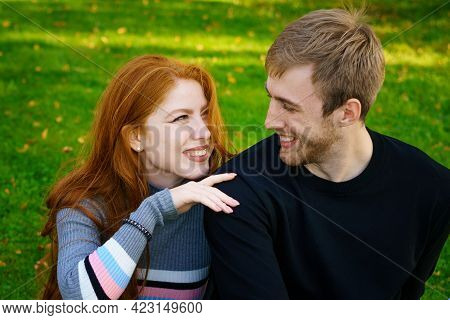 Happy Young Couple Of Caucasian Ethnicity Man And Woman In Casual Clothes Sitting Embracing In The P