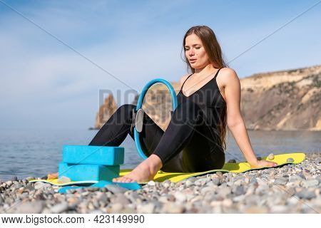 Young Woman With Long Hair, Fitness Instructor In Black Sportswear Leggings And Tops, Stretching On