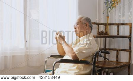 Disabled Elderly Patient Sit On Wheelchair Alone Look Through Window Playing Origami Paper Bird, Sad