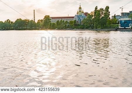 Sunset Light On Water Surface With Church And Industrial Chimney. Sun. Lights. Nature. Lake. River.