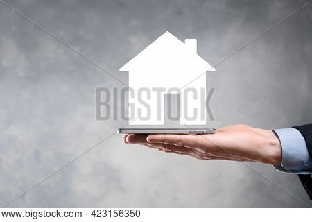 Businessman Male Hand Holding House Icon On Blue Background. Property Insurance And Security Concept