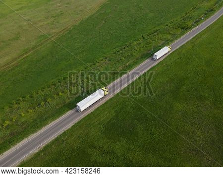 Two Truck with Cargo Semi Trailer Moving on Rural Road in Direction. Aerial Top View