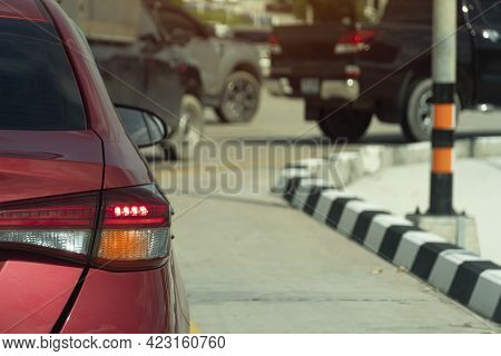 Rear Side Of Red Car Driving On The Road In The City. Watting For U-turn On The Road With Curves Of