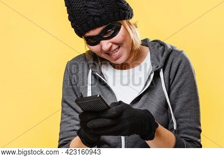 A Female Hacker Wearing A Black Hat, Gloves And Mask Holds A Mobile Phone In Her Hands, Maliciously