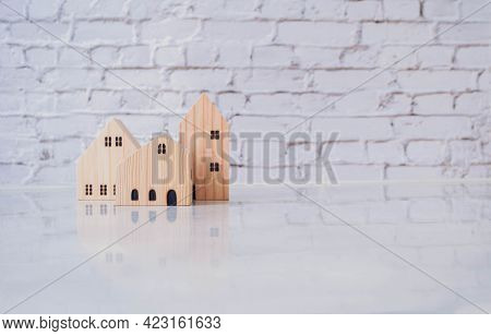 Building Different Miniature Wooden Houses On A White Background. Concept Management Of Real Estate