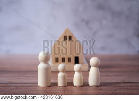 Mini Wood House Model And Wooden Figure Of People In Family Include Parents And Children On Wood Tab
