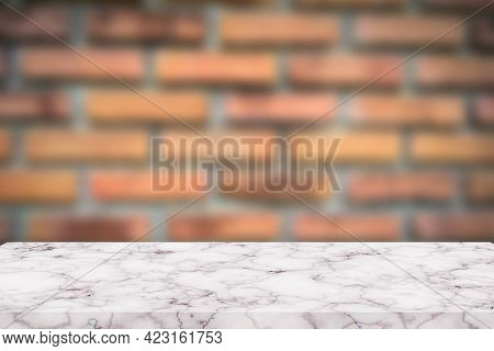 Empty White And Gray Marble Desk For Display Product. Blur Old Orange Brick Wall Background.