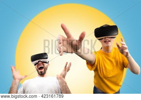 Amazed People Wearing Virtual Reality Glasses Reach For A Virtual Object With Their Hands. Blurred.