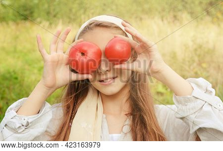 10 Year Old Girl In A White Shirt With 2 Red Tomatoes On A Green Background