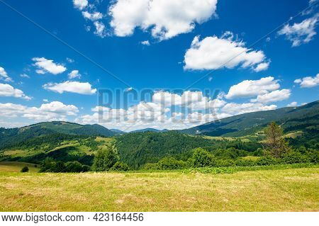 Rural Field In Mountains. Beautiful Nature Landscape. Sunny Summer Day. Clouds On The Sky. Travel Ba