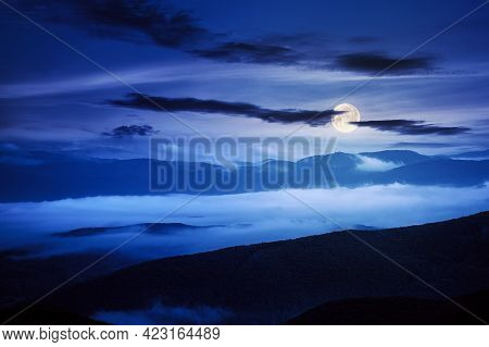 Rural Landscape At Night. Mist In The Distant Valley In Full Moon Light. Silhouette Of Trees And Hil