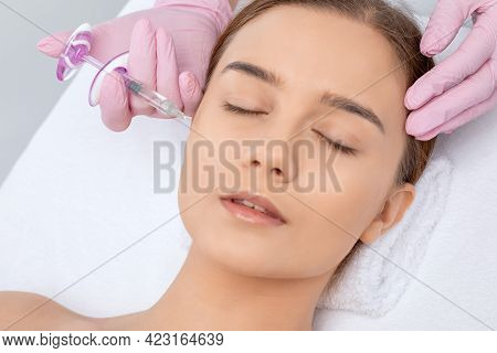 Cosmetologist Makes Rejuvenating Anti Wrinkle Injections On The Face Of A Beautiful Woman. Female Ae