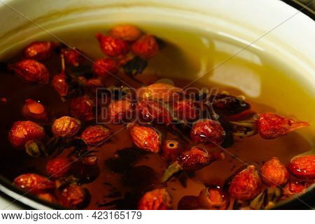 Rose Hips Are Brewed In A Saucepan On A Gas Stove In The Kitchen