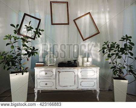 A White Retro Commode With A Record Player, Empty Frames On White Drapery, And Pots Of Plants On The