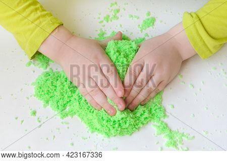 Childrens Hands Close-up, Sculpt, Play With Bright Green Kinetic Sand. The Concept Is The Developmen