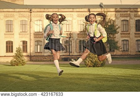 First Day Of Holidays. Happy Kids Run From School. Little Children In Midair Outdoors. School Holida