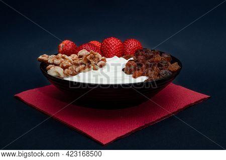 Plain Yogurt With Strawberries, Red Napkin, Raisins, Walnuts And Black Background