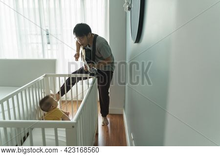 Happy Asian Dad Singing And Playing Acoustic Guitar While Little Adorable Baby Boy Son Sitting In Th