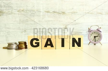 There Are Four Wooden Cubes With Letters On The Table Next To The Coins. Gain Word. On A Gray Backgr