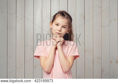 Charming Little Girl 9-11 Years Old In Casual Pink T Shirt, Holding Hands Near Face And Daydreaming,