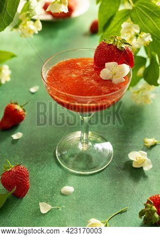 Summer cold berry drink. Strawberry mocktail in glass decorated fresh berry and flower. Summer cocktail on green table surrounded by blooming branches.