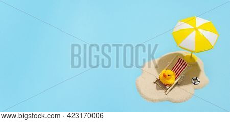 Summer concept. Sun umbrella and duck in sun lounger on sea sand on blue background. Sun protection concept in summer.