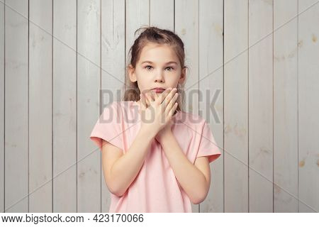 I Am Afraid. Scared Little Girl 9-11 Years Old In Casual Pink T Shirt, Is Cover Opened Mouth Palms A