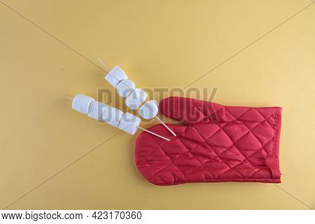 Outing Concept - Spitters With Marshmallows And Red Glove On Yellow Background Flat Lay. Image Conta