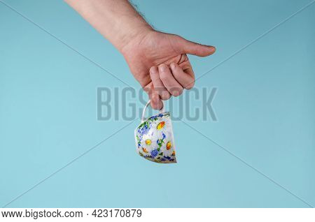 Hand And Cup On Blue Background. Man Holding White Cup With Painted Flowers. Ceramic Mug Cup For Tea