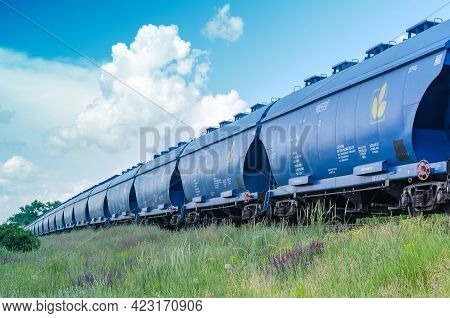 Moving Train With Grain Wagons On The Background Of The Summer Sky. Blue Wagons Full Of Grain Cargo.
