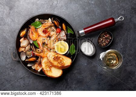 Mixed grilled seafood. Various roasted shrimps, mussels and shellfish in frying pan and white wine. Top view flat lay