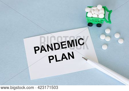 On The Card The Text Of Pandemic Plan, Next To Neatly Decomposed White Tablets With A Pen On A Blue