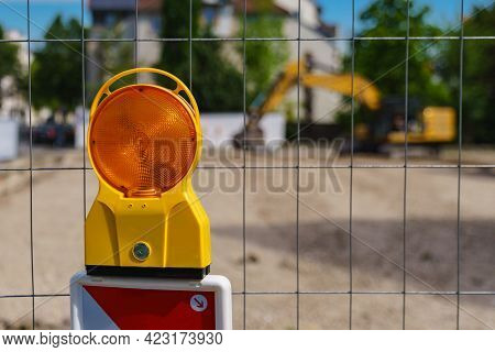 Construction Safety. Street Barricade With Warning Signal Lamp On A Fence. Blur Site Background