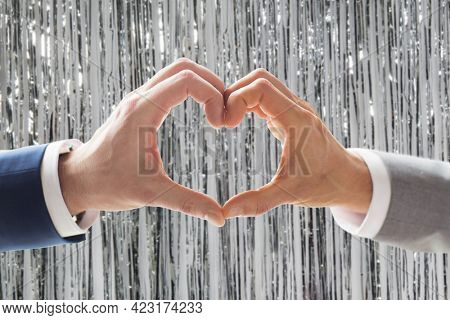 homosexuality, valentines day and love concept - close up of happy male gay couple hands showing heart hand sign over foil party curtain on background