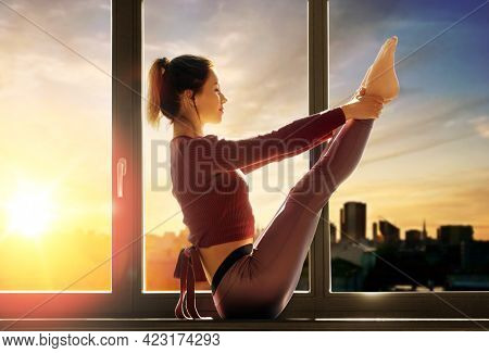 fitness, sport and healthy lifestyle concept - woman doing yoga exercise on window sill at studio over city sunset or sunrise on background